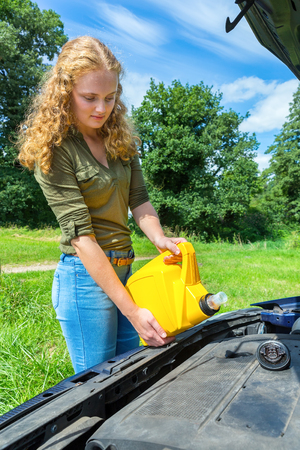 Dutch teenage girl filling car motor with oil from yellow jerrycan