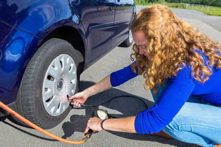 Female car driver checking air pressure of tire outside