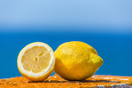 Whole and half yellow lemon with blue sea and sky Stock Photo