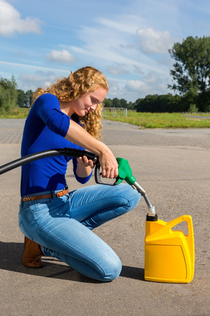 Young dutch woman filling yellow can with gasoline hose outdoors