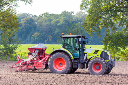 Tractor with agricultural machine on farmland Stock Photo