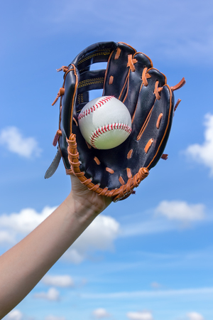 Female arm holding baseball with glove in blue sky Stock Photo
