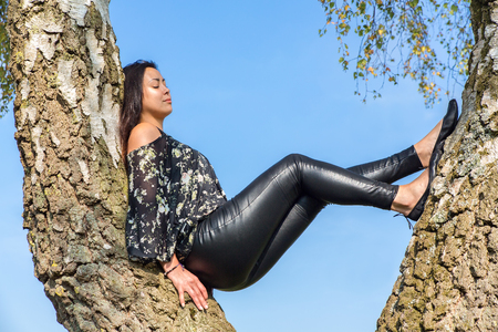 Young woman sitting in birch tree with blue sky