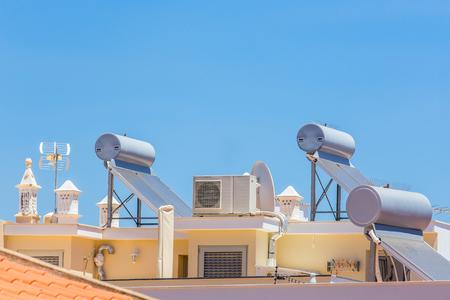 Zonnecollectoren en ketels met airco op dak van huis