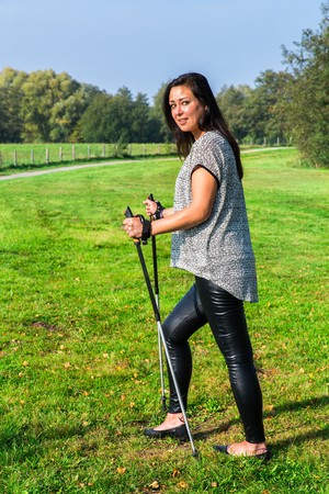 Young woman hiking with Nordic Walking sticks Stok Fotoğraf