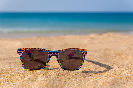 Colorful sunglasses lying on beach with blue sea