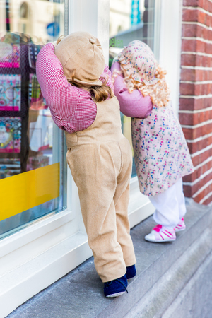Puppets boy and girl look through shop window