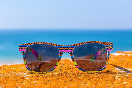 Colorful sunglasses with blue sea and sky Stock Photo