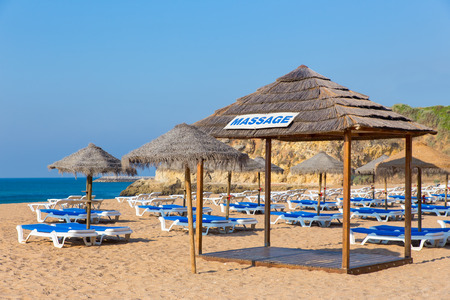 Wicker beach parasols and blue beach beds at sea