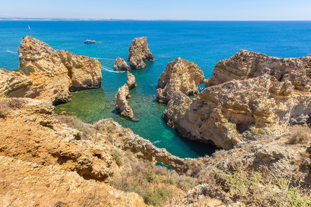 Seashore with rocky mountains and blue ocean in Algarve Portugal Stock Photo