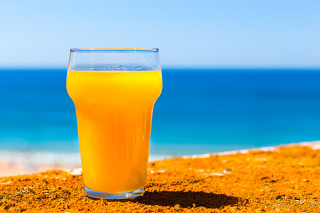 Glass filled with orange juice at blue sea with sky