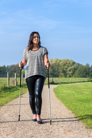 Young woman hiking with Nordic Walking sticks in nature