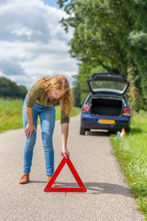 Caucasian teenage girl placing hazard warning triangle on rural road Stock Photo