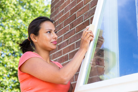 Colombian woman working sanding window outside