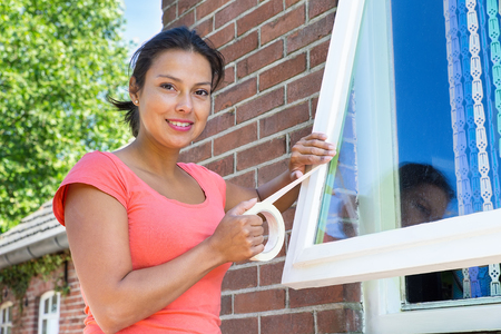 Young colombian woman sticking adhesive tape on window glass