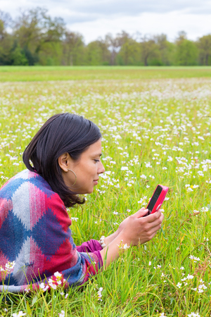 Lying Colombian woman phoning with mobile phone in blooming pasture Stock Photo