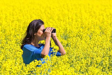 Young woman looking through binoculars in flowering yellow rapeseed field