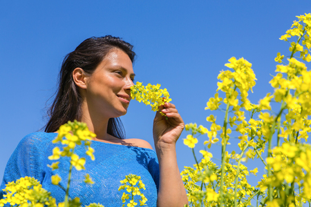 Young colombian woman smells yellow flower in rapeseed field with blue sky Stock Photo