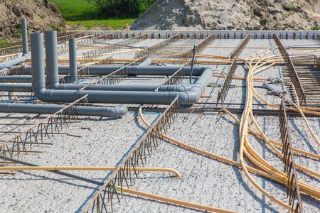 Concrete floor of building with pipes on construction site