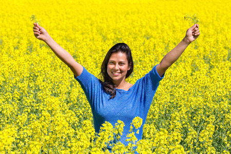 Young happy colombian woman arms up in yellow rapeseed field