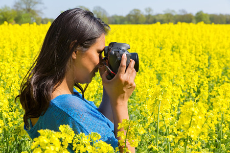 Young colombian woman with camera taking photo of yellow rapeseed field
