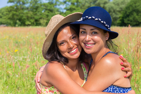Two friends embracing each other in blooming green pasture