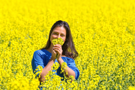 Young Colombian woman smelling yellow flowers in rapeseed field