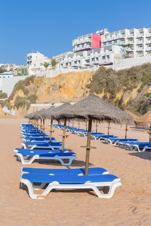 Rows of sunbeds with parasols on portuguese beach in Albufeira