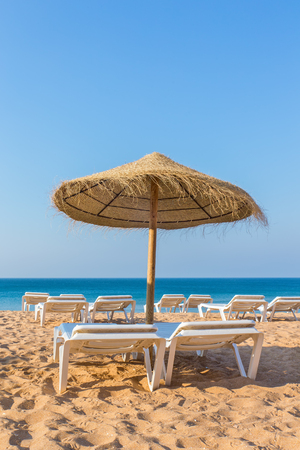 One wicker beach parasol with beach beds at blue sea