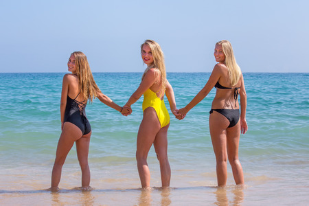 Three blond dutch girls standing hand in hand in blue sea water