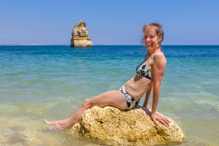 Niederländische Touristin mit Bikini sitzt auf Felsen im Meerwasser Standard-Bild