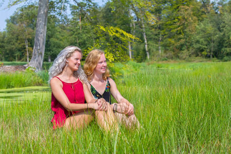 Blond and red-haired woman sitting together in natural meadow