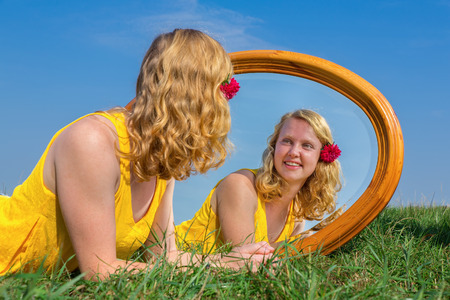 Young red-haired dutch woman lying in grass with mirror Stock Photo