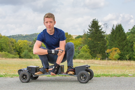 Young caucasian man drives electrical mountainboard on road in nature