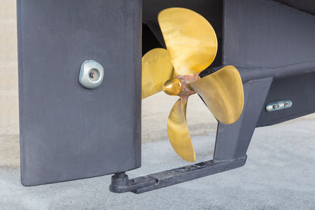 Gold-colored metal propeller and grey rudder of ship Stock Photo