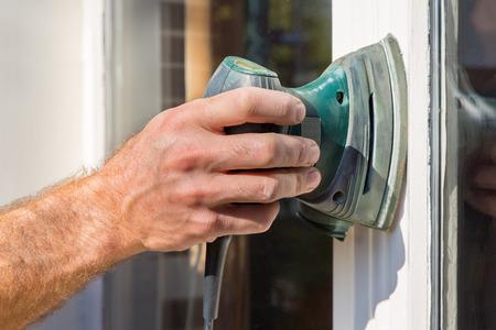 Hand des Malers schleift Fensterrahmen mit Elektroschleifer
