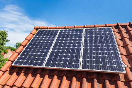 Row of three blue solar collectors  on roof of house Stockfoto