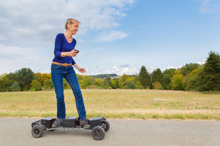 Caucasian woman rides electrical mountainboard on road in nature 免版税图像