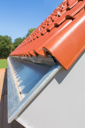 Close up rain gutter with roof tiles at new house