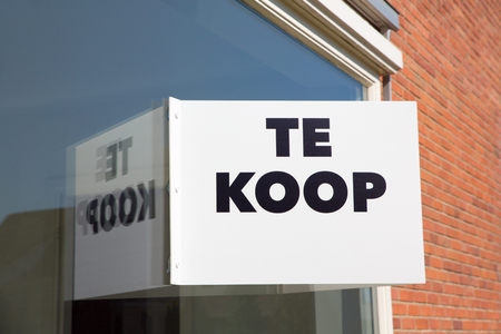 White marketing board on window of home with text Te Koop or For Sale Stock Photo