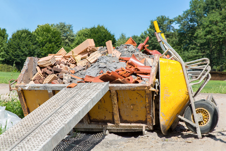 Metal container filled with rubble and wheelbarrow outside