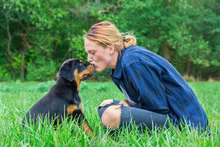 Young caucasian female dog owner  kisses rottweiler puppy on head in natural meadow