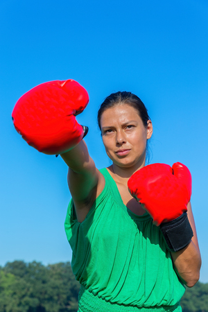 Young colombian woman wears red boxing gloves outdoors Stock Photo