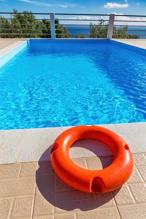 Orange life buoy lies at blue greek swimming pool near coast Фото со стока