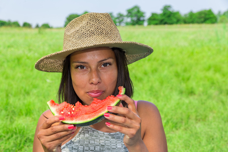 Young colombian woman wearing straw summer hat eating fresh red melon in dutch nature