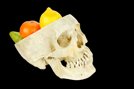 Human skull filled with fruits isolated on black background