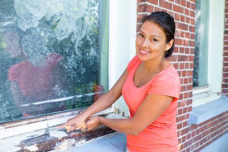 Young colombian woman scrapes with paint scraper over window frame Stock fotó