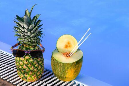 Pineapple wearing sunglasses and melon at blue swimming pool Фото со стока - 131026806