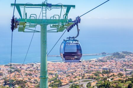 Cable car with cabins above city and sea on island Madeira between Funchal and Monte Фото со стока - 131026812