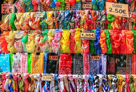 Rows of colorful scarves hanging for sale at market in Madeira Фото со стока - 131026845